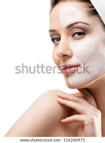 Woman in headband with lifting cream applied on a half of her face, isolated on white