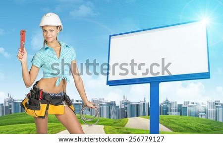 Woman in helmet and tool belt with different tools holding wrench and two flexible hoses, smiling. Green hills with road, buildings and empty billboard as backdrop
