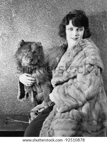 Woman in her fur coat sitting with her dog