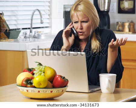 Woman in her kitchen on cell phone sitting in front of laptop. Computer problems?