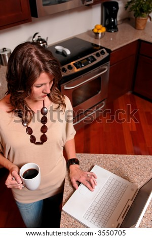 woman in her 30's standing in the kitchen with coffee and laptop computer -- top view