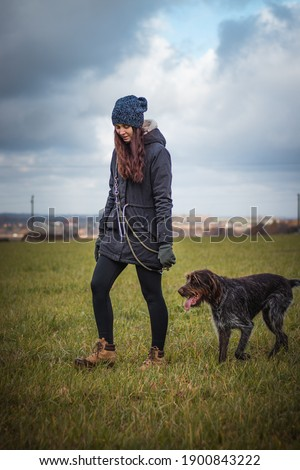 woman in her 20-24s walks her dog through the fields. Bohemian Wire-haired Pointing Griffon obediently clings to his mistress and protects her from any danger. Candid portrait of pet and girl. Foto stock ©