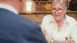 Woman in her sixties telling her husband an interesting story during mealtime in a restaurant. Couple talking. Relaxed couple. Two pensioners.