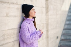 Woman in her twenties leaning against a wall outside with her eyes closed. Lifestyle concept.