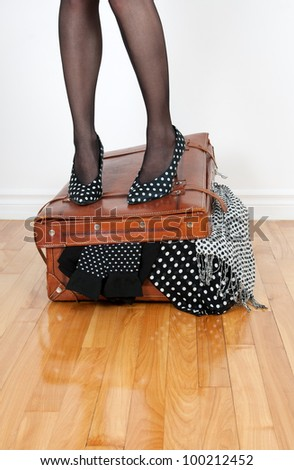 Woman in high heel shoes standing on leather suitcase overfilled with fashion clothing.