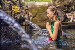 Woman in holy spring water temple in bali. The temple compound consists of a petirtaan or bathing structure, famous for its holy spring water