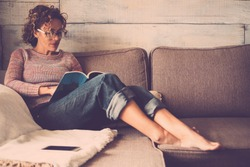 woman in home sitting on sofa reading book