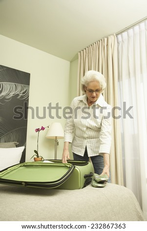 Woman in Hotel Room Unpacking her Suitcase