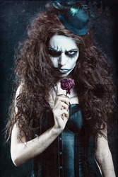 Woman in image of a gothic freak clown with withered flower. Grunge texture effect