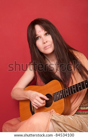 Woman in Indian outfit holds guitar over red background