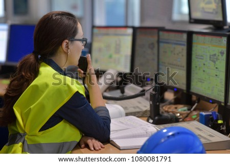 Woman in industrial control room using radio to give instructions