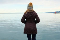 Woman in jacket and hat looking at the sea during winter walks on the beach, view from the back