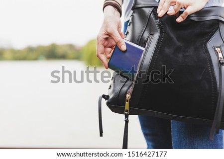 Woman in jeans pulling out mobile phone from a leather bag's pocket outdoors - Female dressed in denim pants trying to put a telephone Stock foto ©