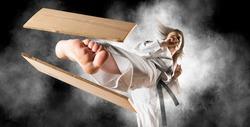Woman in kimono practicing. Fighter concept. Breaking board. Smoke background