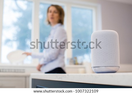 Woman In Kitchen Asking Digital Assistant Whilst Washing Up #1007322109