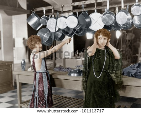 Woman in kitchen beating on pots and pans - stock photo
