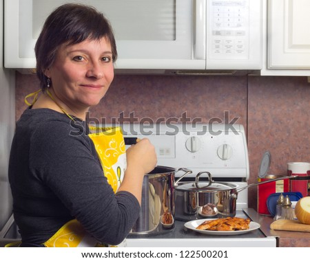 Woman in kitchen cooking a meal on the stove
