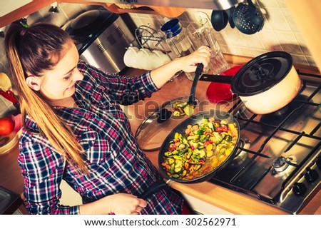 Woman in kitchen cooking stir fry frozen vegetables. Girl frying making delicious dinner food meal. Instagram filtered.