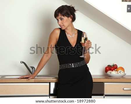 Woman in kitchen on a home party with champagne