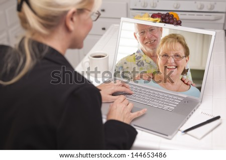 Woman In Kitchen Using Laptop - Online Chat with Senior Couple or Parents On Screen.
