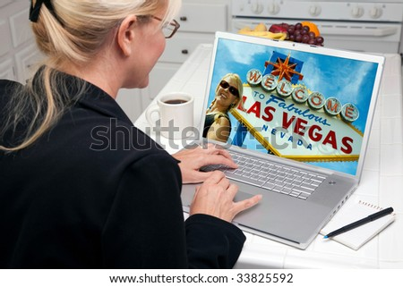 Woman In Kitchen Using Laptop to Research A Las Vegas Trip. Screen image can easily be replaced using the included clipping path.