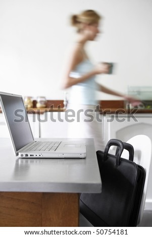 Woman in kitchen walking by laptop, focus on laptop