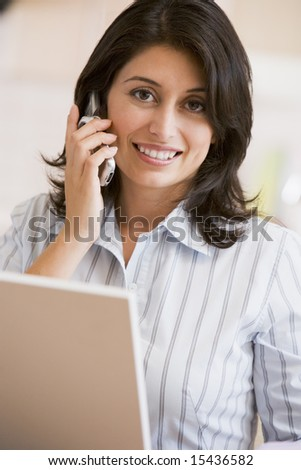 Woman in kitchen with laptop and cellular phone smiling