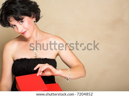 Woman in lace black dress with short curly hair, wearing pearls, opening a red gift box