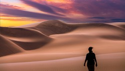 woman in landcape with awesome sunset sky over Namib Desert in Namibia, southern Africa