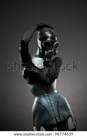 Woman in latex corset and gas mask, studio shot on black background