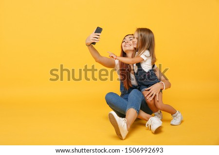 Woman in light clothes doing selfie with cute child baby girl 4-5 years old. Mommy little kid daughter isolated on yellow background studio portrait. Mother's Day family parenthood childhood concept