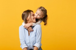 Woman in light clothes have fun with cute child baby girl 4-5 years old. Mommy little kid daughter isolated on yellow background studio portrait. Mother's Day love family parenthood childhood concept