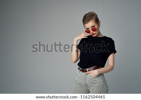 woman in light pants and in a dark T-shirt, fashion glasses                            #1162504465