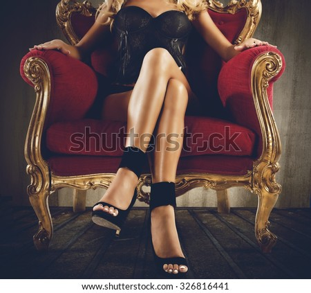Woman in lingerie sitting on an armchair