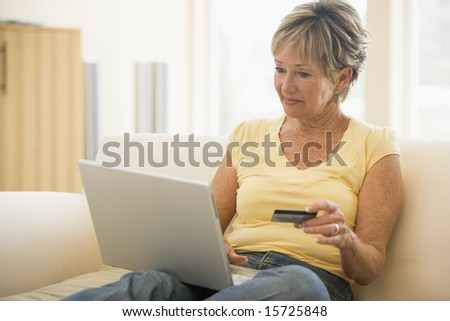 Woman in living room with laptop and credit card smiling