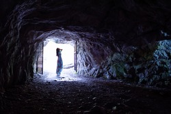 Woman in long dress standing near exit from the cave