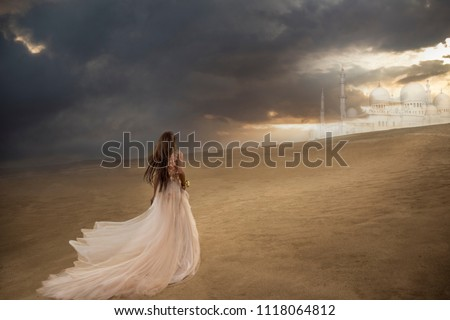 Woman in long dress walking in the desert towards palace in the distance
