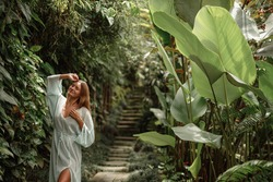 Woman in long elegant silk dress posing in tropical garden, closed eyes, happy and smiling