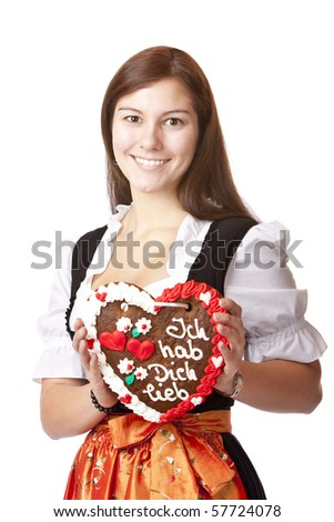 Woman in love dressed with Oktoberfest dirndl holding gingerbread heart. Isolated on white background.