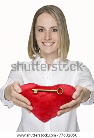 Woman in love holding red heart with a golden key on it