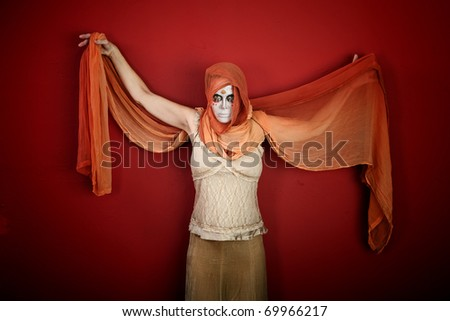 Woman in makeup for All Souls Day with scarf spreading her arms on red background