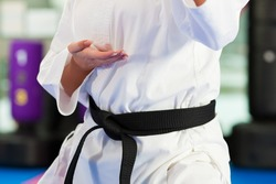 Woman in martial art training in a gym, she is wearing a black belt