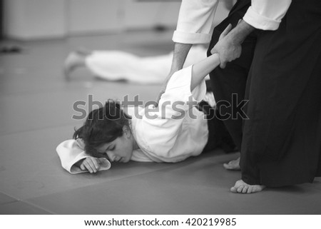 Woman in martial arts; young woman lying on the mat  #420219985