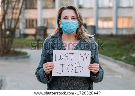 Woman in mask holds sign lost my job. Concept of job loss due to COVID-19 virus pandemic. Female stands against background of business center