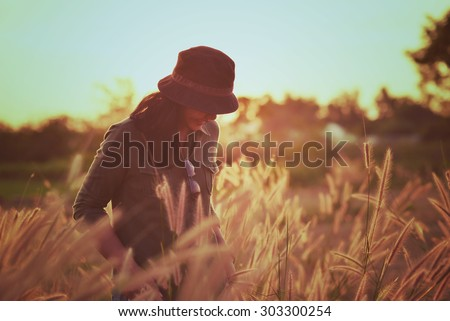 Woman in meadow. travel and sunset in vintage style