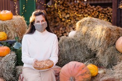 Woman in medical mask celebrates Thanksgiving 2020. Tradition cake decoration. Coronavirus protection social distance loneliness. Face cover pandemic homemade. Hello, Autumn quarantine