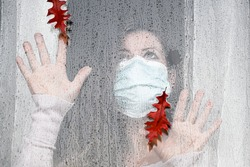 Woman in medical mask indoors looking through glass window in raindrops looks at falling autumn leaves. Second wave of coronavirus Covid-19.Autumn concept. Bad rainy weather. Stay home.Quarantine