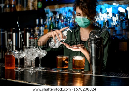 Woman in medical mask treats her hands with disinfector behind bar counter. Medical mask for prophylaxis and protection from coronavirus. Glasses and tools for making cocktail stand on bar counter. Photo stock ©