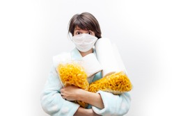 Woman in medical mask with toilet paper and packs of pasta representing panic buying during the coronavirus COVID-19 pandemic in 2019-2020 - isolated on white background
