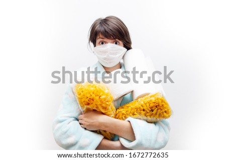 Woman in medical mask with toilet paper and packs of pasta representing panic buying during the coronavirus COVID-19 pandemic in 2019-2020 - isolated on white background Foto stock ©